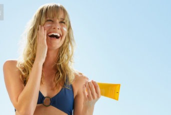 Woman putting on all-natural sunscreen